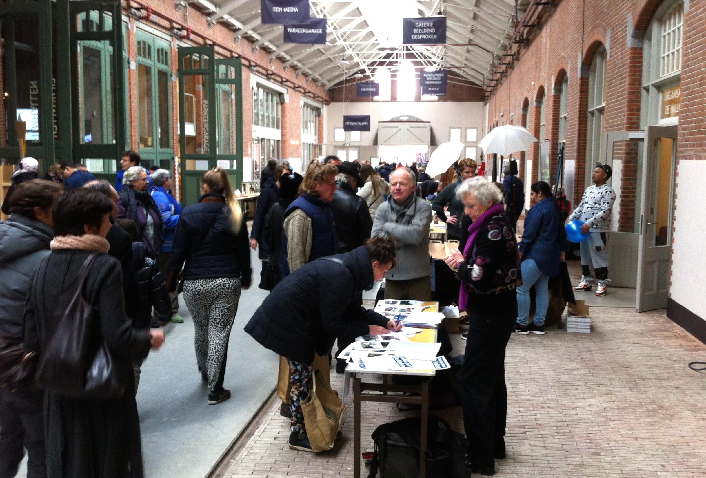 Een buurtbewoner zet in De Hallen haar handtekening tegen overlast door de vele bezoekers.
